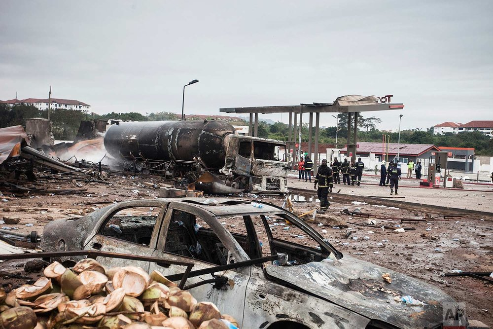 Firefighters stand at the site of the previous day's gas tanker explosion in Accra, Ghana, on Sunday Oct. 8, 2017. (AP Photo/Richmond Brentuo)