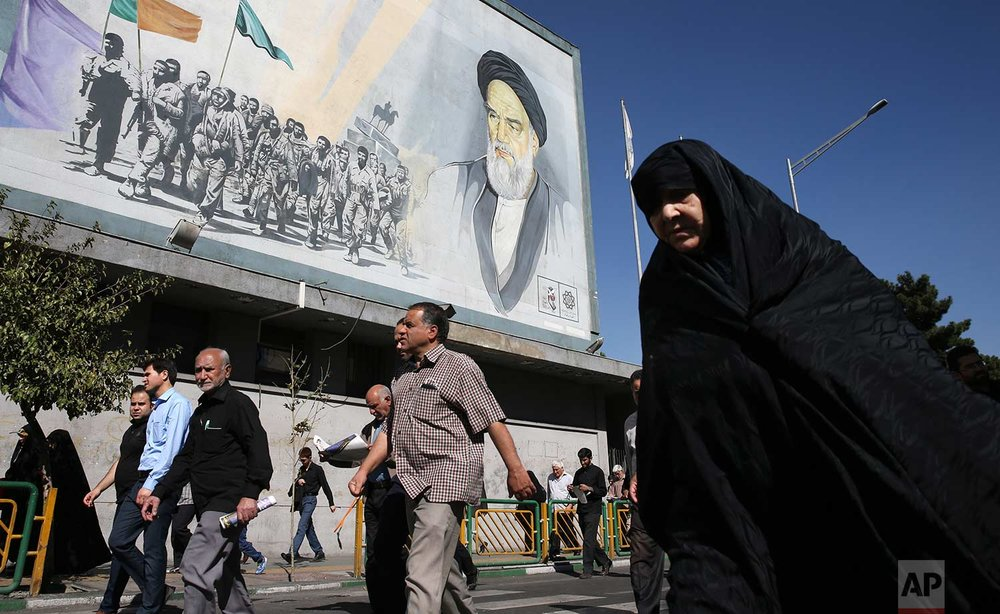Iranian worshippers walk past a painting of the late revolutionary founder Ayatollah Khomeini and Basij paramilitary force members, at the conclusion of a Friday prayer ceremony in Tehran, Iran, Friday, Oct. 13, 2017. (AP Photo/Vahid Salemi)