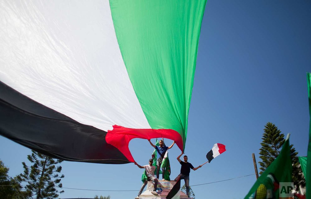 Palestinians waving national and Egyptian flags celebrate the reconciliation agreement between Hamas and Fatah in Egypt, in Gaza City, Thursday, Oct. 12, 2017. (AP Photo/Khalil Hamra)