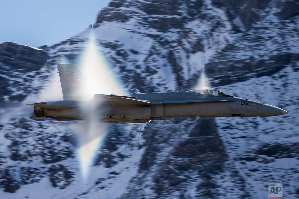 A Swiss Air Force F/A-18 Hornet fighter jet performs a high-speed flyby breaking the sonic barrier as pilots demonstrate their skills in the Swiss Alps above Axalp Ebenfluh on Tuesday, Oct. 10, 2017.(Christian Merz/Keystone via AP)