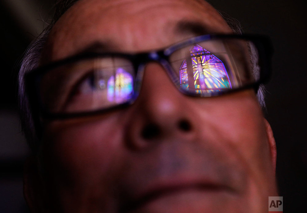 "Wayne Christopher stands for a portrait in Port Arthur, Texas, Monday, Sept. 25, 2017, as a stained glass window is reflected in his glasses in the damaged sanctuary of the Memorial Baptist Church he'd attended his whole life. After the previous month's Hurricane Harvey, he said, ""I think the Lord put us over the care of his creation, and when we pollute like we do, destroy the land, there's consequences to that,"" he said. ""And it might not catch up with us just right now, but it's gonna catch up. Like a wound that needs to be healed."" (AP Photo/David Goldman)"
