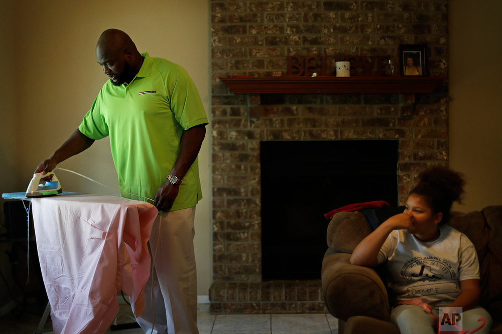 "Joe Evans, a Jefferson County Republican, left, irons his shirt in the home he shares with his daughter Denver, 11, and two other daughters, not pictured, in Beaumont, Texas, Tuesday, Sept. 26, 2017. Evans voted for Trump, but he's frustrated with what he describes at the ""conservative echo chamber"" that calls climate change a hoax instead of trying to find a way to apply conservative principles to simultaneously saving the earth and the economy. ""I haven't put so much thought into it that I want to go mobilize a bunch of people and march on Washington,"" he said. ""But it made me think enough about it that I won't actively take part in denying it. I won't actively take part in calling it a hoax. We can't do that anymore."" (AP Photo/David Goldman)"