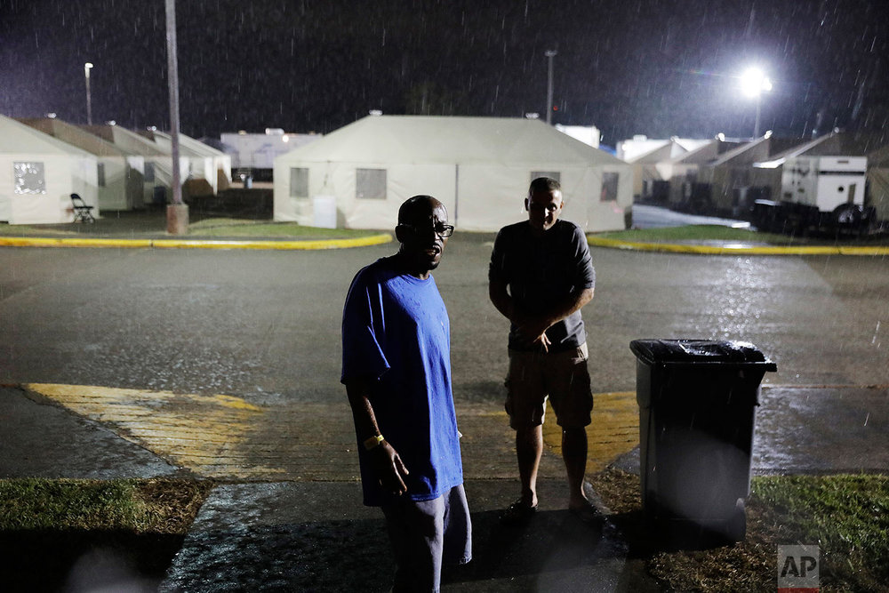 Arthur Shields, left, and a fellow evacuee walk through a temporary shelter encampment in Port Arthur, Texas, Wednesday, Sept. 27, 2017, where they've been living for nearly a month since hurricane Harvey damaged their homes. Jefferson County was drowned by more than 60 inches of rain during Hurricane Harvey, the most rainfall ever recorded in a single storm in the nation's history, according to preliminary data from the National Weather Service. (AP Photo/David Goldman)