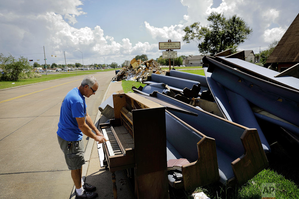 "Wayne Christopher plays the keys on a piano put out on the curb in Port Arthur, Texas, Monday, Sept. 25, 2017, next to pews from the Memorial Baptist Church which he'd attended his whole life. The damage was caused by Hurricane Harvey a month earlier. ""He's not too up on global warming, and that's a shame,"" Christopher said of the president he supported in November, and supports still. He also believes in the consensus among scientists that climate change is real and that this disastrous run of weather, from droughts in the west to wildfires to catastrophic hurricanes along the coasts, is a preview of the future if the country doesn't begin to take the problem seriously. (AP Photo/David Goldman)"