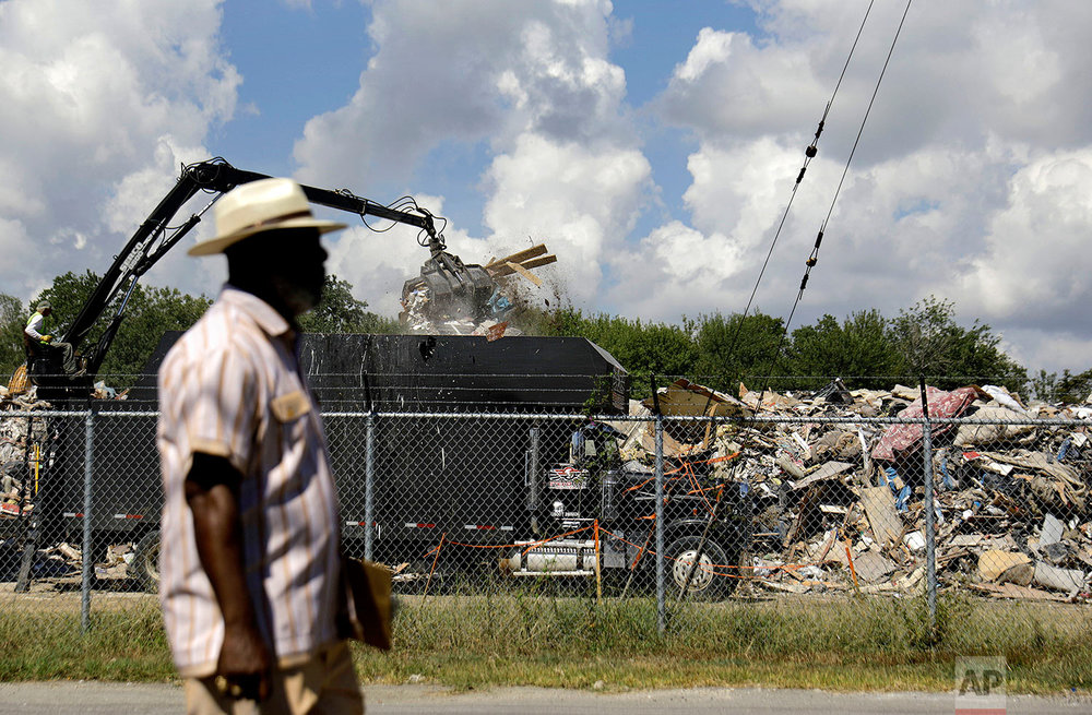 "Hilton Kelley walks by as a truck unloads flood damaged debris at a makeshift dump across the street from a residential neighborhood in Port Arthur, Texas, Wednesday, Sept. 27, 2017. Kelley is fighting to get the dump shut down for fear of nearby residents breathing in mold. Kelley says many people in Port Arthur understand the impact local industry has on climate change and pollution. But he says they're often hesitant to speak out. ""When you have people living at or below the poverty line, many people are hopeful of getting jobs at those refineries or chemical plants."" (AP Photo/David Goldman)"