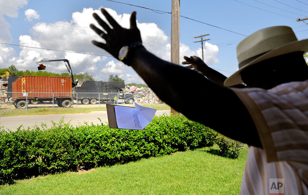 "Hilton Kelley tosses his petition clipboard in frustration as he's turned away from a renter who was told by her landlord not to get involved in Kelley's attempt to shutdown the dump across the street piled with flood damaged debris in Port Arthur, Texas, Wednesday, Sept. 27, 2017. ""This is an outrage. This is appalling. There's no way this should have happened,"" said Kelly of the dump's proximity to people's homes. He worried about mold and other contaminants from the garbage getting into the low-income African American neighborhood. These are the neighborhoods, he said, that often pay the price for environmental pollution. Many of these neighborhoods also flooded. (AP Photo/David Goldman)"