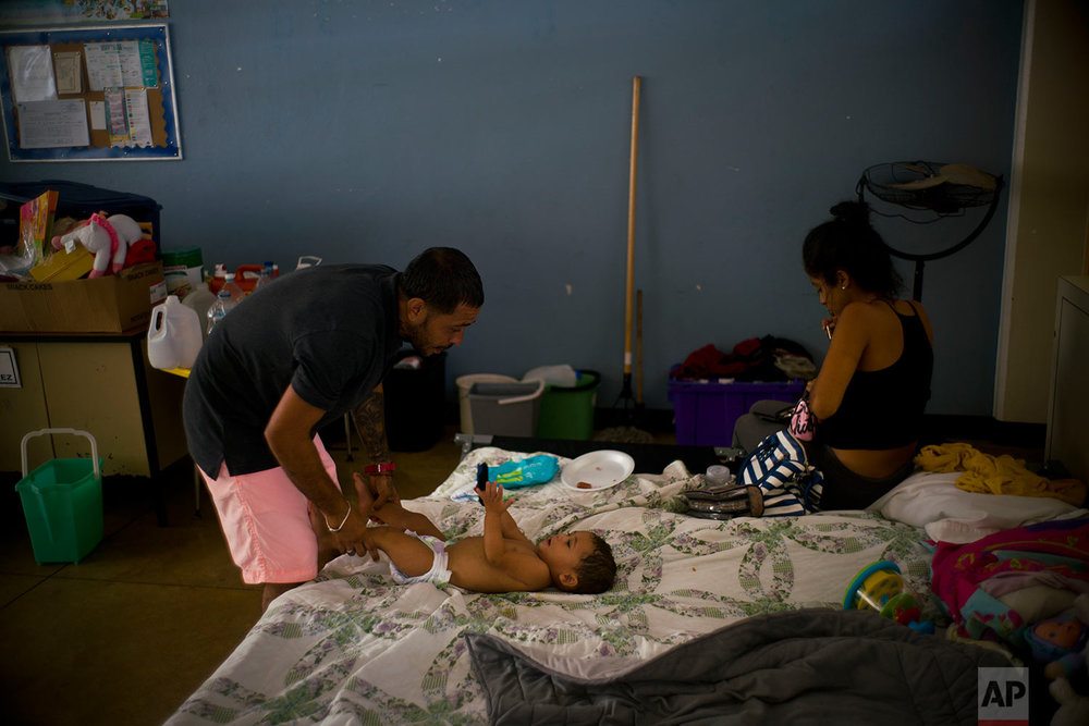 In this Friday, Oct. 13, 2017 photo, Arden Dragoni changes his baby's diaper as his wife Sindy puts on her makeup on their bed inside a classroom at a school serving as a shelter for people left homeless by Hurricane Maria in Toa Baja, Puerto Rico. (AP Photo/Ramon Espinosa)