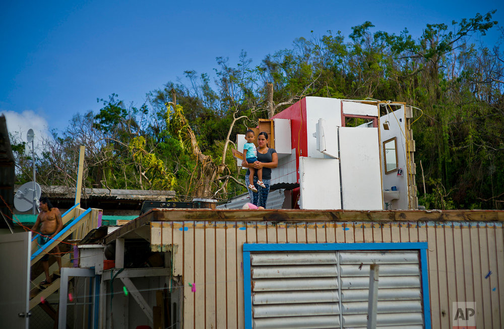 In this Saturday, Oct. 14, 2017 photo, Silvie Lise Santiago holds her daughter on the floor of their home, the floor above her father's home, both of which were destroyed by Hurricane Maria, as she talks to her neighbor Arden Dragoni, not in picture, who was also left homeless in Toa Baja, Puerto Rico.  (AP Photo/Ramon Espinosa)