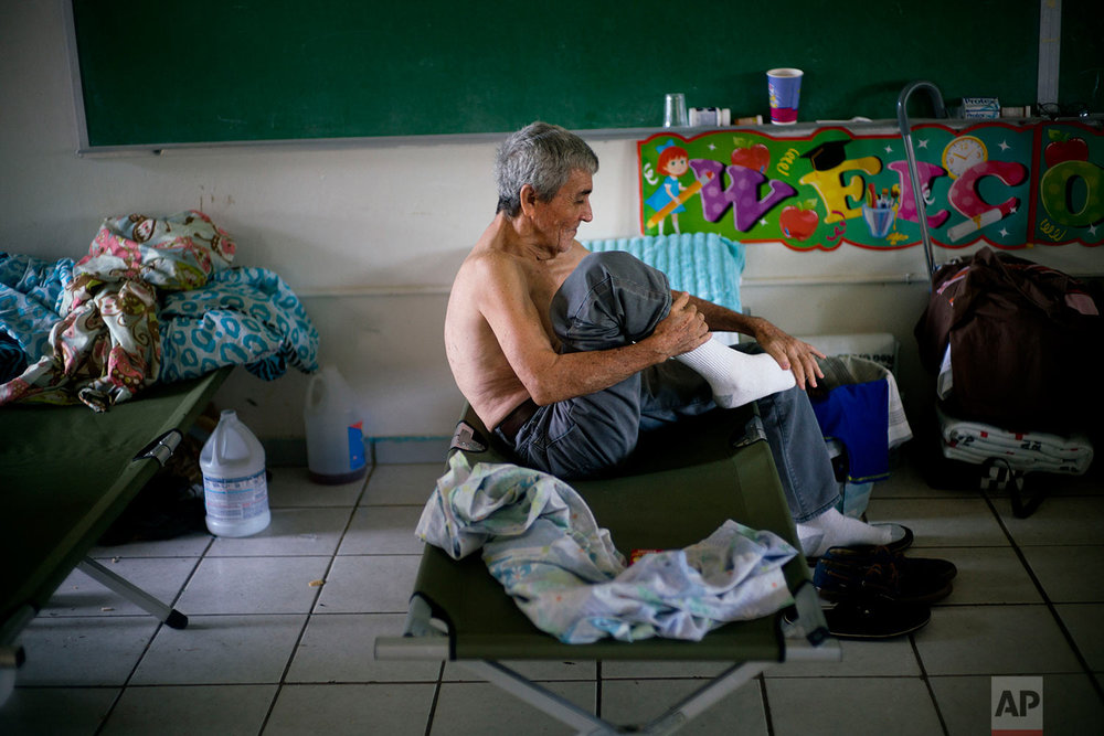 In this Thursday, Oct. 12, 2017 photo, Jesus Soto Rosado puts his socks on after spending the night at a school-turned-shelter for residents left homeless by Hurricane Maria in Toa Baja, Puerto Rico. (AP Photo/Ramon Espinosa)