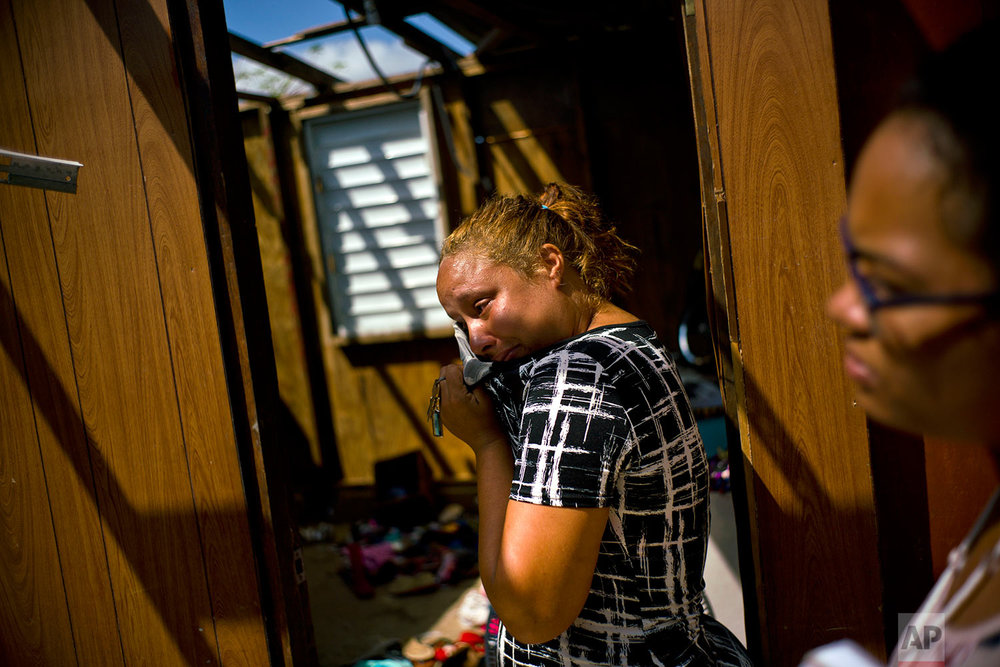 In this Thursday, Oct. 12, 2017 photo, Midiam Rivera Cruz cries as she surveys her storm destroyed home with a Housing Ministry official in Toa Baja, Puerto Rico. (AP Photo/Ramon Espinosa)