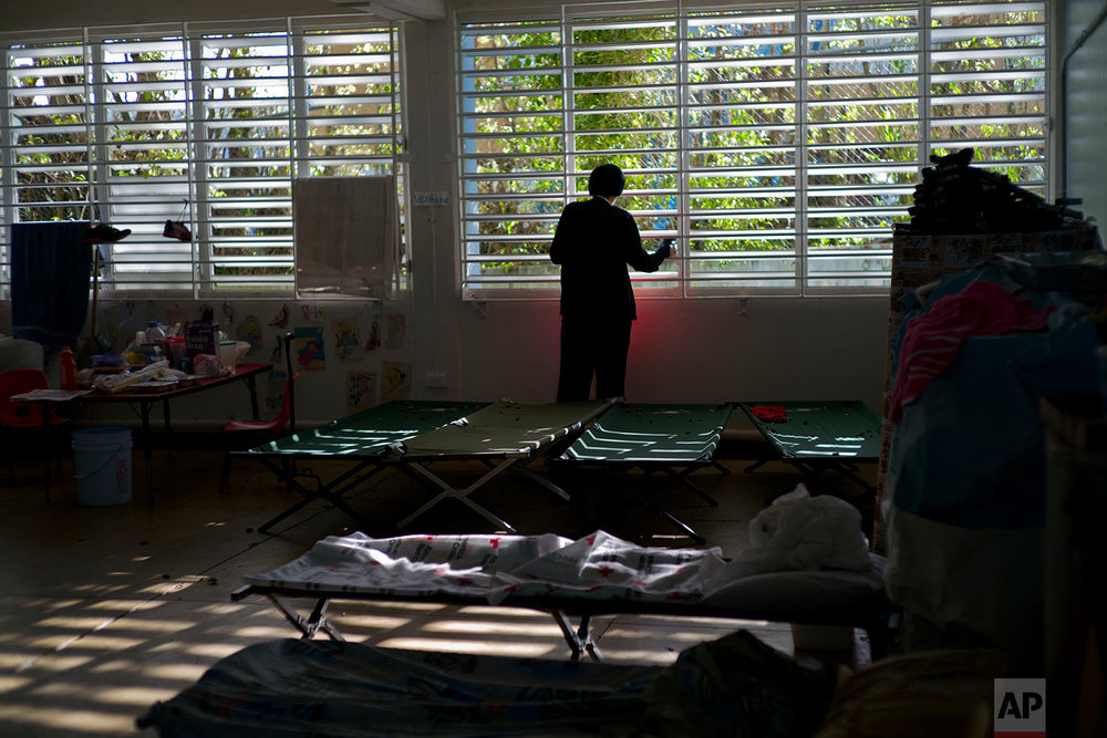 In this Thursday, Oct. 12, 2017 photo, a teenager left homeless by Hurricane Maria looks out the window of the school-turned-shelter where he's living in Toa Baja, Puerto Rico. (AP Photo/Ramon Espinosa)