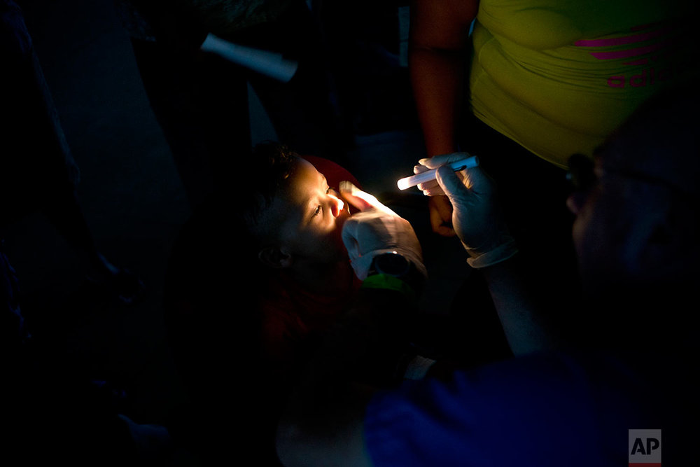 In this Friday, Oct. 13, 2017 photo, a doctor gives a general check-up to a child living in a shelter set up at a school for residents left homeless by Hurricane Maria in Toa Baja, Puerto Rico. (AP Photo/Ramon Espinosa)