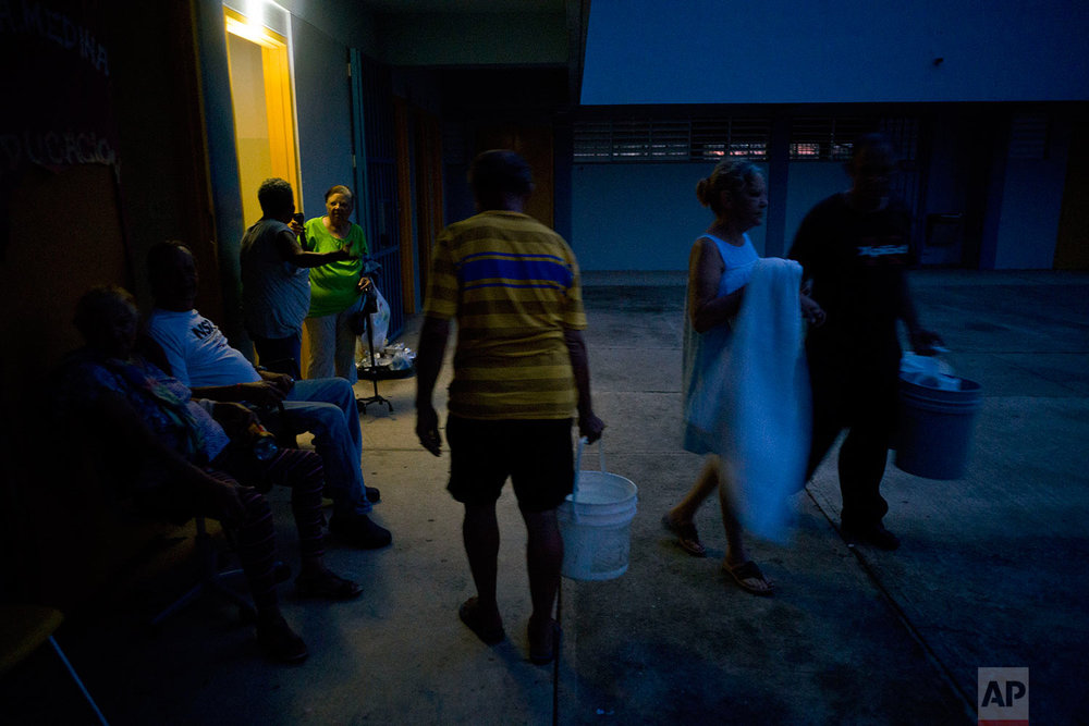 In This Thursday, Oct. 12, 2017 photo, people left homeless by Hurricane Maria carry buckets of water for bathing and cleaning, at a school-turned-shelter that does not have electricity in Toa Baja, Puerto Rico. (AP Photo/Ramon Espinosa)