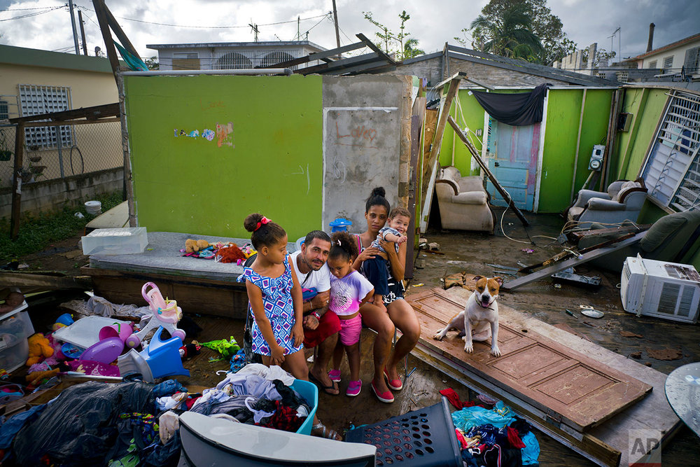 In this Saturday, Oct. 14, 2017 photo, Arden Dragoni, second from left, poses with his wife Sindy, their three children and dog Max, surrounded by what remains of their home destroyed by Hurricane Maria in Toa Baja, Puerto Rico. The Dragoni family has been living in a shelter set up at a school since the storm destroyed their wooden home in late September. They lost everything: clothes, household goods, and an old car. Dragoni supported his family by working construction, but his employers are currently out of business, leaving him and his family without a source of income. (AP Photo/Ramon Espinosa)
