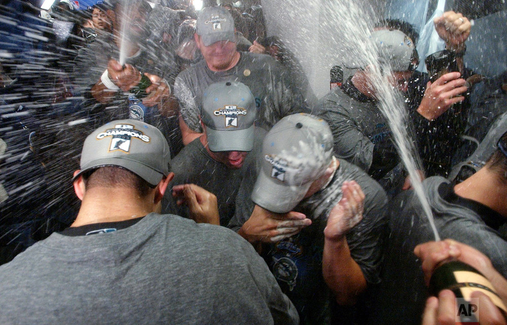 Champagne flies in the Florida Marlins' locker room after they won the World Series over the New York Yankees in Game 6 of the World Series Saturday, Oct. 25, 2003 in New York. (AP Photo/Charles Krupa)