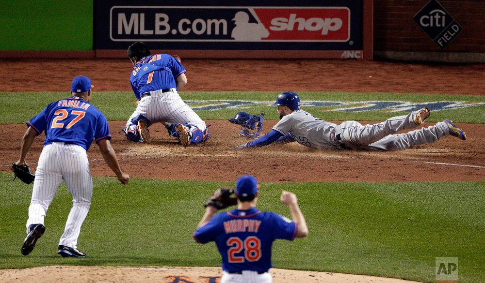 Kansas City Royals' Eric Hosmer right, scores past New York Mets catcher Travis d'Arnaud as relief pitcher Jeurys Familia (27) and second baseman Daniel Murphy (28) look on during the ninth inning of Game 5 of the Major League Baseball World Series Sunday, Nov. 1, 2015, in New York. (AP Photo/Charlie Riedel)