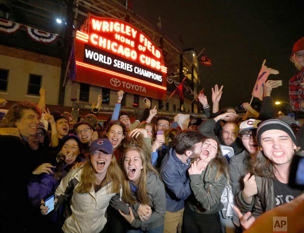 Chicago Cubs fans celebrate in front of Wrigley Field in Chicago on Wednesday night, Nov. 2, 2016, after the Cubs defeated the Cleveland Indians 8-7 in Game 7 of the baseball World Series in Cleveland. (AP Photo/Charles Rex Arbogast)