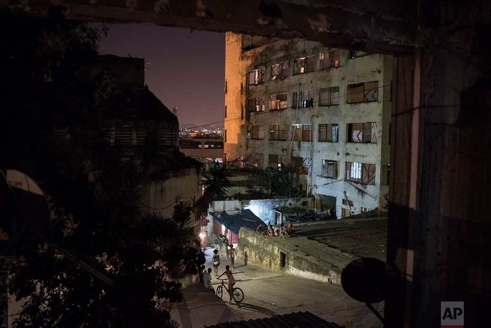 In this Sept. 12, 2017 photo, residents walk by a building that used to house the Brazilian Institute of Geography and Statistics, (IBGE), in the Mangueira slum of Rio de Janeiro, Brazil. The IBGE has become home to hundreds of squatters. (AP Photo/Felipe Dana)