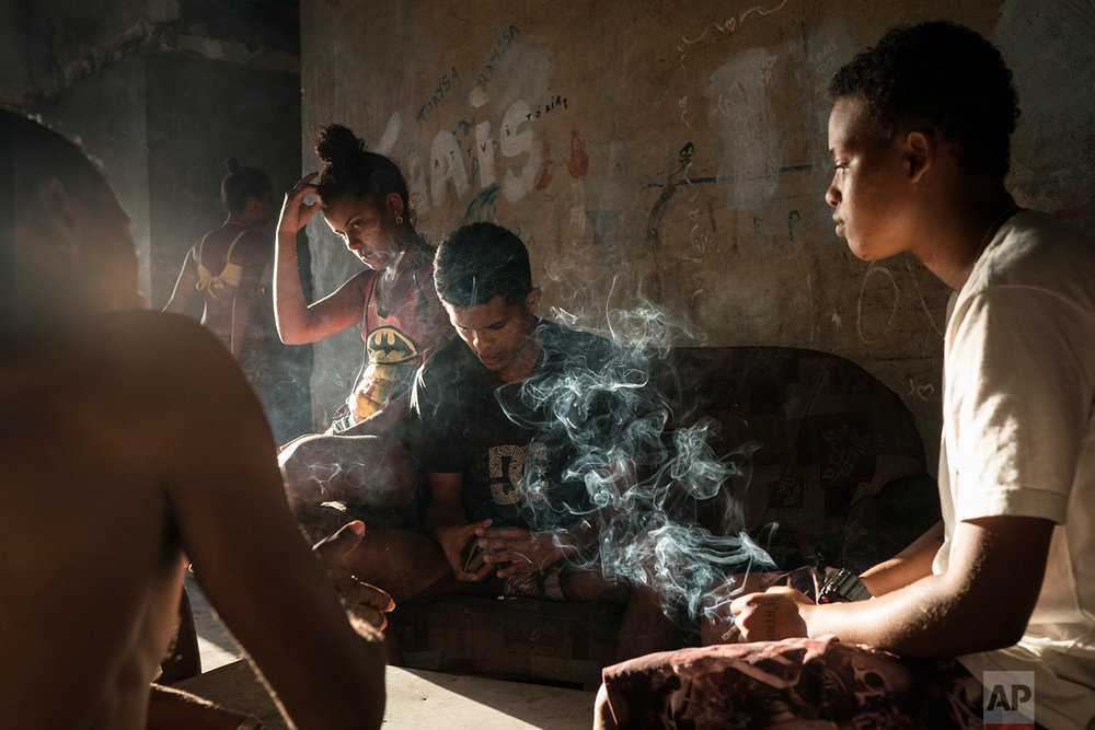 In this Sept. 16, 2017 photo, Jayanne Pessanha, right, smokes a cigarette while playing cards with neighbors in a squatter building that used to house the Brazilian Institute of Geography and Statistics (IBGE) in the Mangueira slum of Rio de Janeiro, Brazil. Pessanha, 20, said her sister died a few years ago after falling from an empty window, and her brother died when he hit his head during a fight. (AP Photo/Felipe Dana)