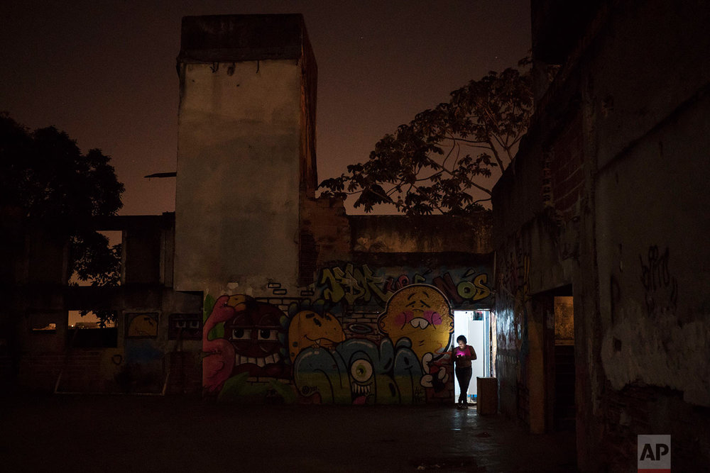"In this Sept. 9, 2017 photo, a woman stands at the entrance of her home inside a squatter building that used to house the Brazilian Institute of Geography and Statistics (IBGE) in the Mangueira slum of Rio de Janeiro, Brazil. Brazil's ""boom"" decade is eroding, with millions of its people returning to poverty amid recession, corruption and cuts to social welfare programs. (AP Photo/Felipe Dana)"