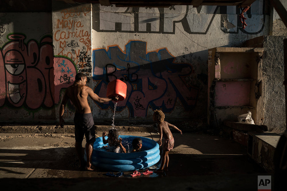 In this Sept. 11, 2017 photo, children play as a man fills a small plastic pool with water at a squatter building that used to house the Brazilian Institute of Geography and Statistics (IBGE) in the Mangueira slum of Rio de Janeiro, Brazil. Economists say that high unemployment and cuts to key social welfare programs could exacerbate some Brazilians' slide back into poverty. (AP Photo/Felipe Dana)