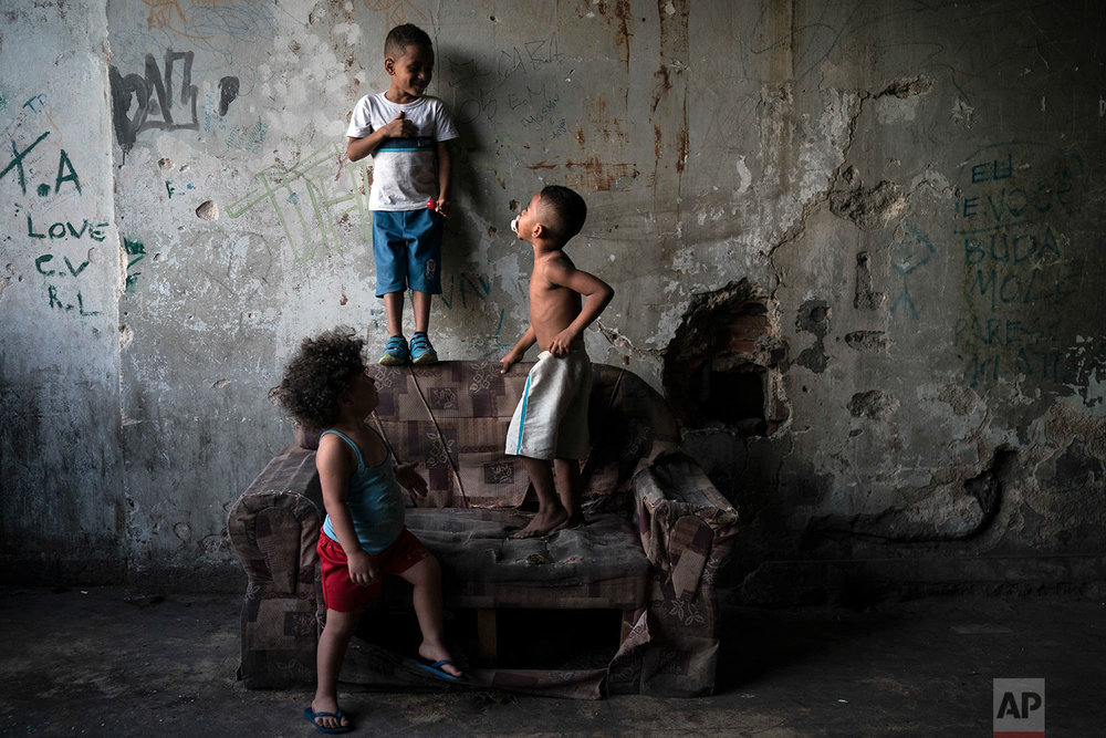 "In this Sept. 11, 2017 photo, children play inside a squatter building that used to house the Brazilian Institute of Geography and Statistics (IBGE) in the Mangueira slum of Rio de Janeiro, Brazil. Budgetary pressures and the conservative policies of President Michel Temer are translating into cuts in social services, including the ""Bolsa Familia"" program that gives monthly small subsidies to qualifying low-income people. (AP Photo/Felipe Dana)"