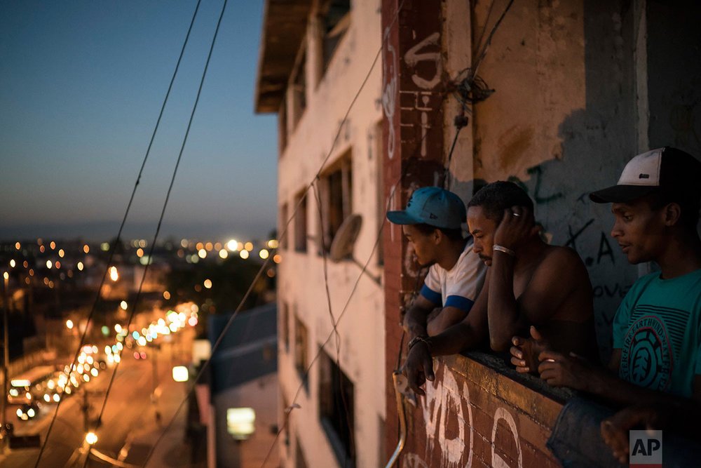 In this Sept. 14, 2017 photo, residents look out from a balcony inside a squatter building that used to house the Brazilian Institute of Geography and Statistics (IBGE) in the Mangueira slum of Rio de Janeiro, Brazil. On the campaign trail, former President Luiz Inacio Lula da Silva promises both a return to better economic times and refocusing on the poor. (AP Photo/Felipe Dana)