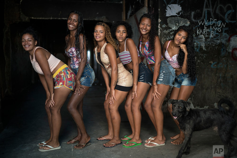 In this Sept. 14, 2017 photo, young women pose for a photo inside their squatter building that used to house the Brazilian Institute of Geography and Statistics (IBGE) in the Mangueira slum of Rio de Janeiro, Brazil. Many lower-middle class Brazilians who gained ground during the boom years have since slid back closer to the poverty line. (AP Photo/Felipe Dana)