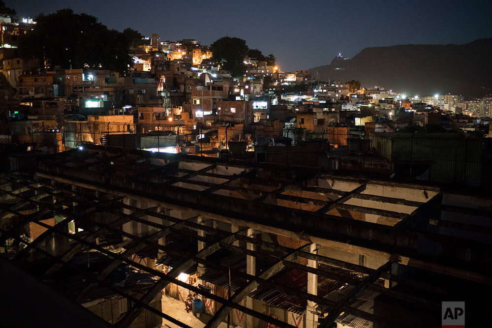 This Sept. 10, 2017 photo shows a night view of the Mangueira slum, seen from a squatter building that used to house the Brazilian Institute of Geography and Statistics IGBE) in the Mangueira slum of Rio de Janeiro, Brazil. A confluence of factors is raising the specter that this continent-sized nation, which has one of the world's largest economies, has lost its way in addressing vast inequalities that go back to colonial times. (AP Photo/Felipe Dana)