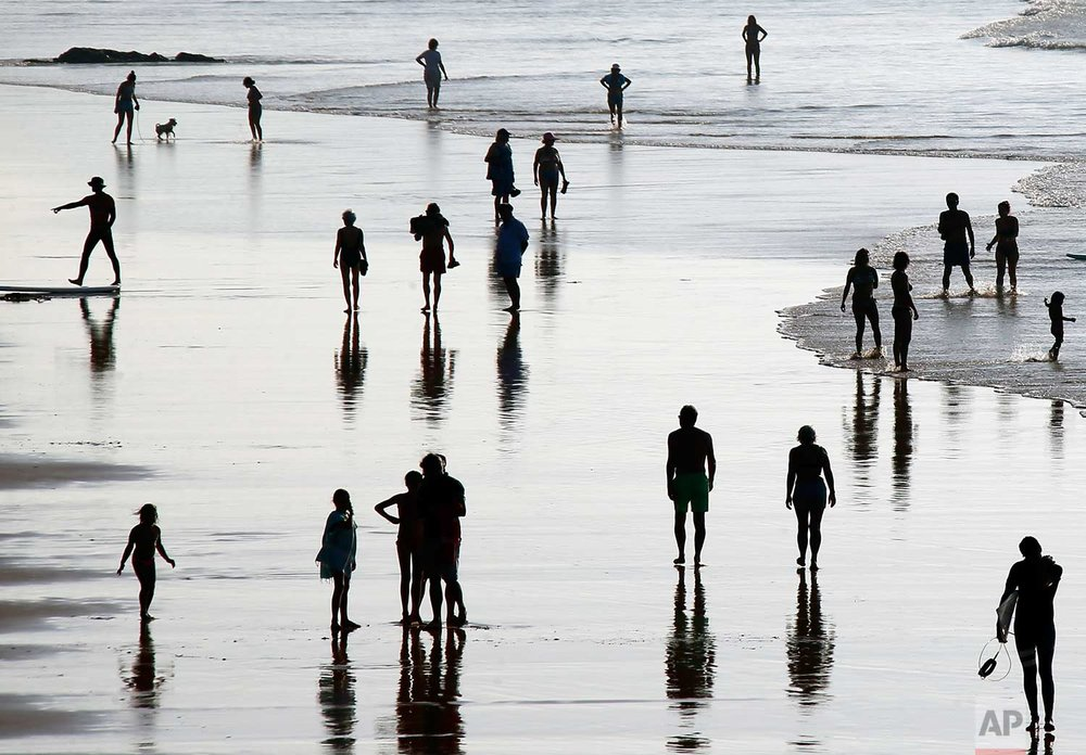 People walk on the beach in Biarritz, southwestern France, Saturday, Oct. 14, 2017. (AP Photo/Bob Edme)