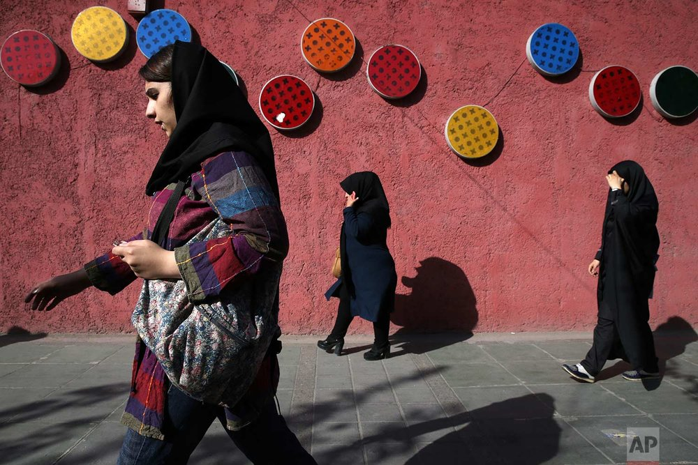 Pedestrians walk down a sidewalk in downtown Tehran, Iran, Saturday, Oct. 14, 2017. (AP Photo/Vahid Salemi)