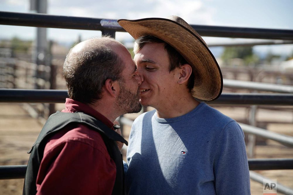 In this Sept. 23, 2017, photo, Wesly Dickson, right, kisses Chris Tobin after Tobin competed at the Bighorn Rodeo, a gay rodeo, in Las Vegas. (AP Photo/John Locher)