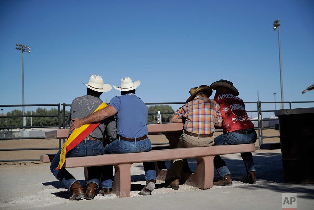 In this Sept. 24, 2017, photo, Jim Applegate, left, Mr. Palms Springs Hot Rodeo, is embraced by Jimmy Warner as they watch the Bighorn Rodeo in Las Vegas. (AP Photo/John Locher)
