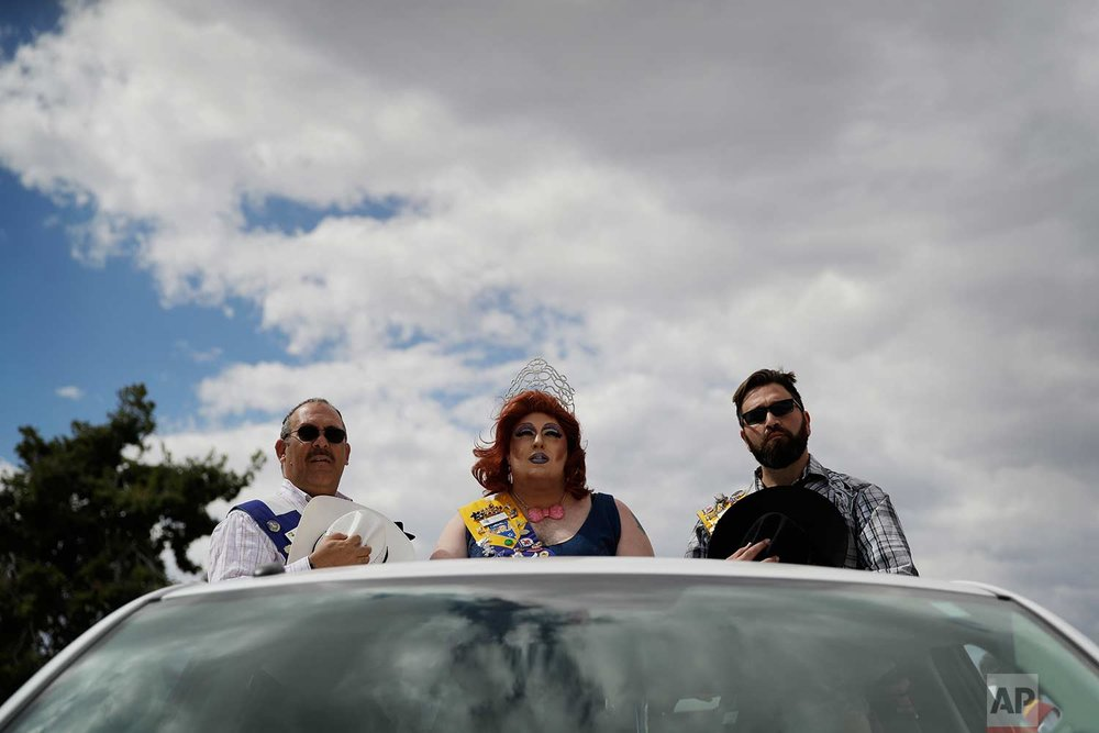 In this Sept. 23, 2017, photo, Jason Dyer, from left, First runner up Mr. Nevada Gay Rodeo, Phat Patty CarMichael, Miss Nevada Gay Rodeo, and Brian Porras, Mr. Nevada Gay Rodeo, stand in the back of a pickup truck before the grand entry at the Bighorn Rodeo in Las Vegas. (AP Photo/John Locher)