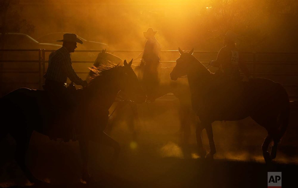 In this Sept. 23, 2017, photo, competitors ride horses in a warm-up area before competing in the Bighorn Rodeo in Las Vegas. (AP Photo/John Locher)