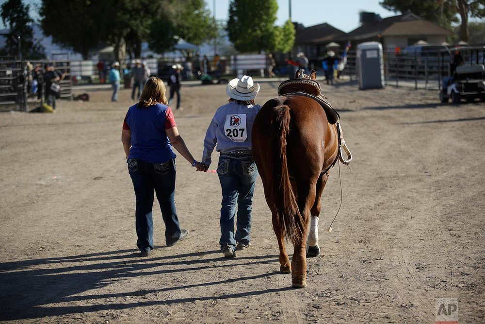In this Sept. 24, 2017, photo, two people holds hands during a break in the Bighorn Rodeo in Las Vegas. (AP Photo/John Locher)