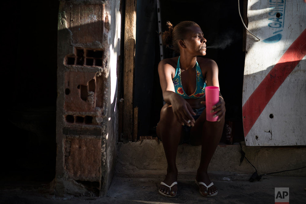 In this Sept. 14, 2017 photo, Leticia Miranda sits at her doorstep in the former Brazilian Institute of Geography and Statistics (IBGE) building in the Mangueira favela of Rio de Janeiro, Brazil. When Miranda, 28, lost her job selling newspapers about six months ago amid Brazil's worst economic crisis in decades, she had no choice but to move to an abandoned building where several hundred people were already living. (AP Photo/Felipe Dana)