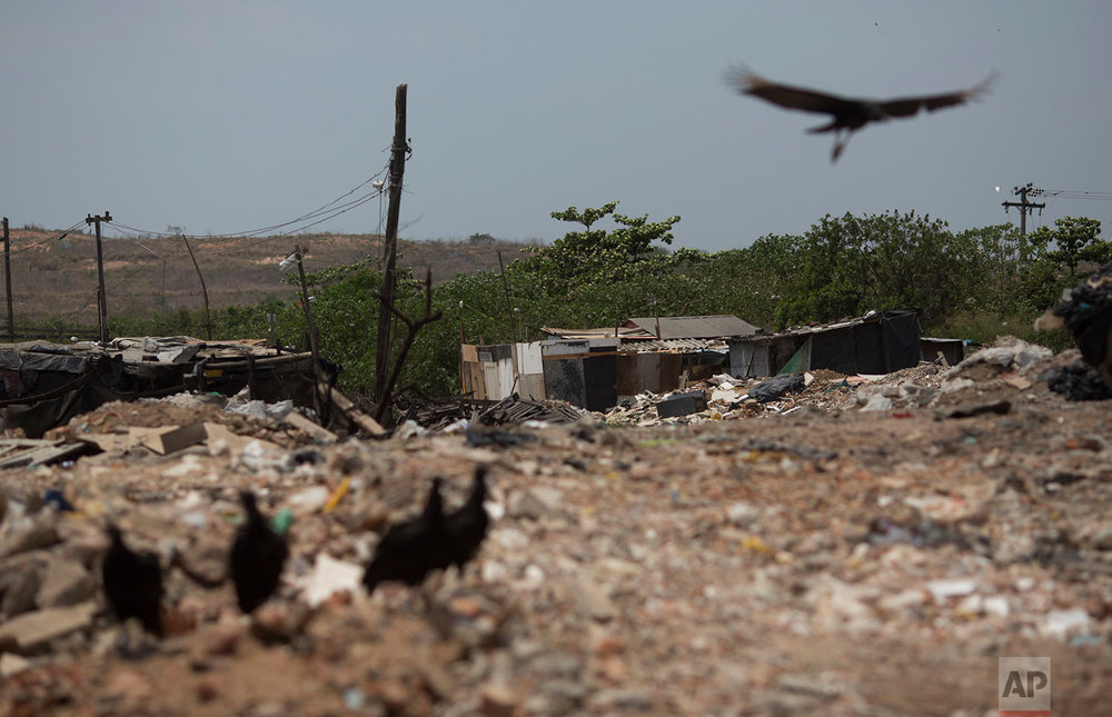 In this Oct. 20, 2017 photo, vultures fly near people's shack homes in the Jardim Gramacho slum of Rio de Janeiro, Brazil. Brazil's trend of people emerging from poverty has reversed over the last two years due to the deepest recession in Brazil's history and cuts to the subsidy programs, raising the specter that this continent-sized nation has lost its way in addressing massive inequalities that go back to colonial times. (AP Photo/Silvia Izquierdo)