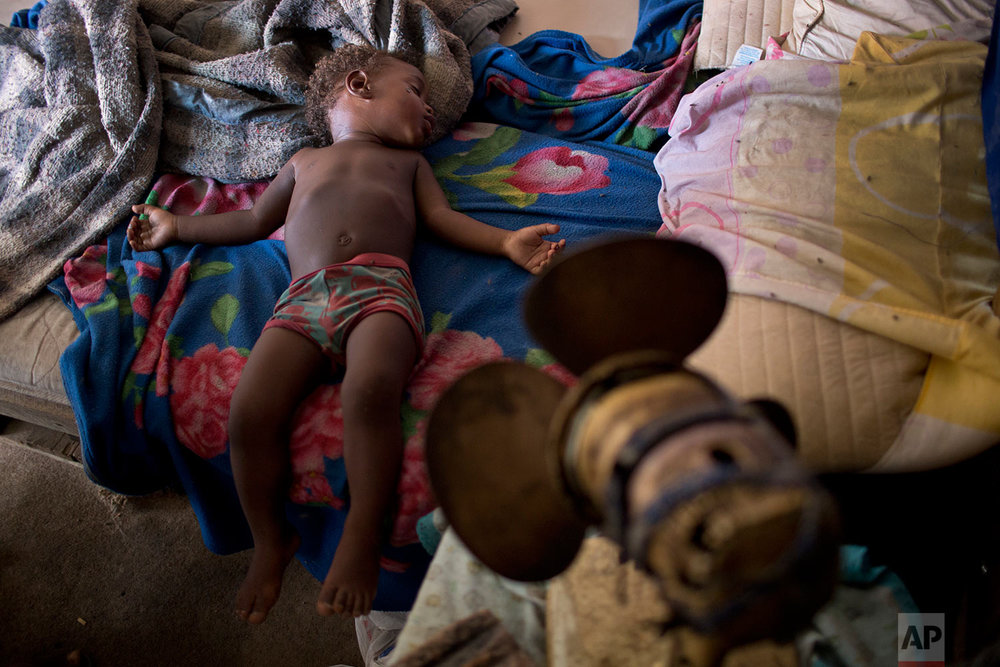 "In this Oct. 20, 2017 photo, Simone Batista's 1-year-old son Arthur sleeps under a fan that no longer works in the Jardim Gramacho slum of Rio de Janeiro, Brazil. After Arthur was born, his mother was cut from the ""Bolsa Familia"" government subsidy for low-income families, a program credited with much of the poverty reduction during Brazil's boom decade. (AP Photo/Silvia Izquierdo)"