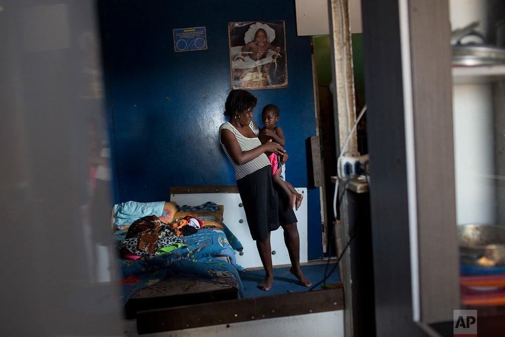 In this Oct. 20, 2017, Vanessa holds her son Gabriel inside their home in the Jardim Gramacho slum of Rio de Janeiro, Brazil. For many who live in Rio's hundreds of slums, like Vanessa who makes detergent to sell, an already hardscrabble existence feels increasingly precarious. (AP Photo/Silvia Izquierdo)