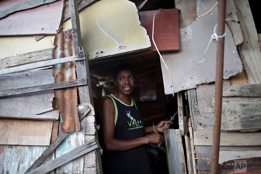 In this Sept. 26, 2017 photo, a man who said he does odd jobs to get by, stands at the entrance of his shack on a hillside in the Lins slum of Rio de Janeiro, Brazil. In July, the last month for which data is available, Brazil's unemployment was close to 13 percent, a huge increase from 4 percent at the end of 2004. (AP Photo/Silvia Izquierdo)