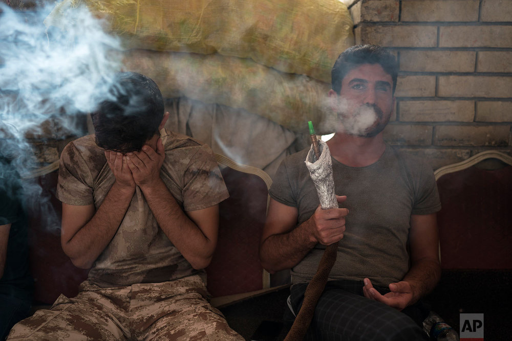 Kurdish men smoke a water pipe in central Irbil, Iraq, Wednesday, Oct. 25, 2017. In Sept. 2017, Iraq's Kurds celebrated their symbolic vote for independence, but instead of moving forward with negotiations toward a smooth divorce from Baghdad, they have lost their most important oil-producing city to Iraqi troops, squeezing a hurting economy and dashing the hopes of an independent state. (AP Photo/Felipe Dana)