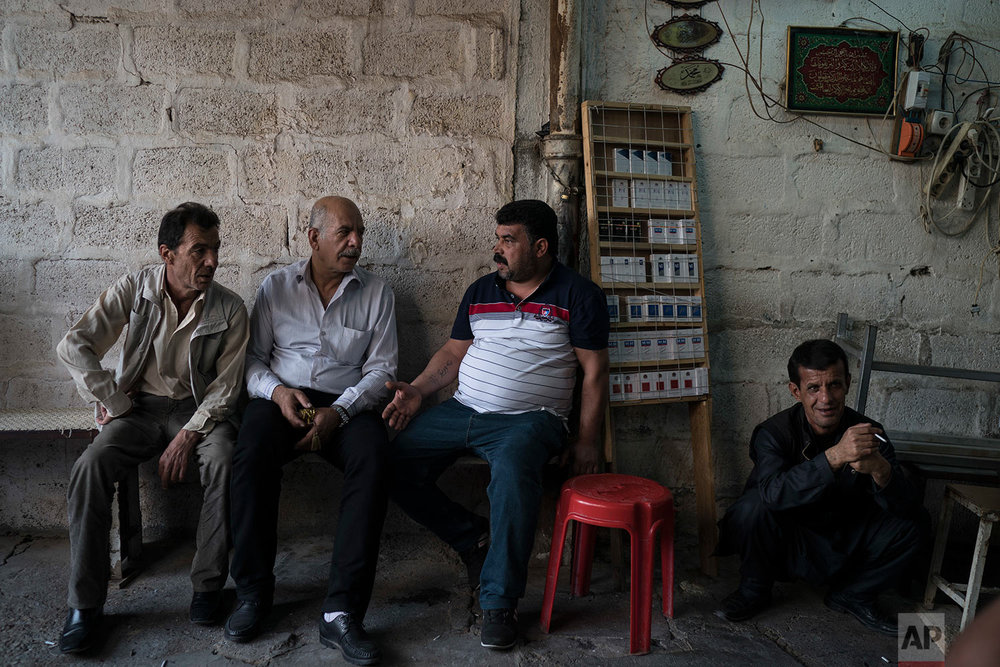 Kurdish men sit outside a tea shop in central Irbil, Iraq, Wednesday, Oct. 25, 2017. In Sept. 2017, Iraq's Kurds celebrated their symbolic vote for independence, but instead of moving forward with negotiations toward a smooth divorce from Baghdad, they have lost their most important oil-producing city to Iraqi troops, squeezing a hurting economy and dashing the hopes of an independent state. (AP Photo/Felipe Dana)