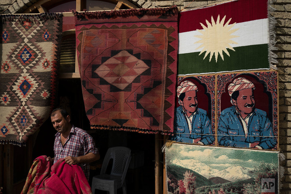 A man sells rugs depicting Kurdish president Masoud Barzani, right, in central Irbil, Iraq, Wednesday, Oct. 25, 2017. In Sept. 2017, Iraq's Kurds celebrated their symbolic vote for independence, but instead of moving forward with negotiations toward a smooth divorce from Baghdad, they have lost their most important oil-producing city to Iraqi troops, squeezing a hurting economy and dashing the hopes of an independent state. (AP Photo/Felipe Dana)