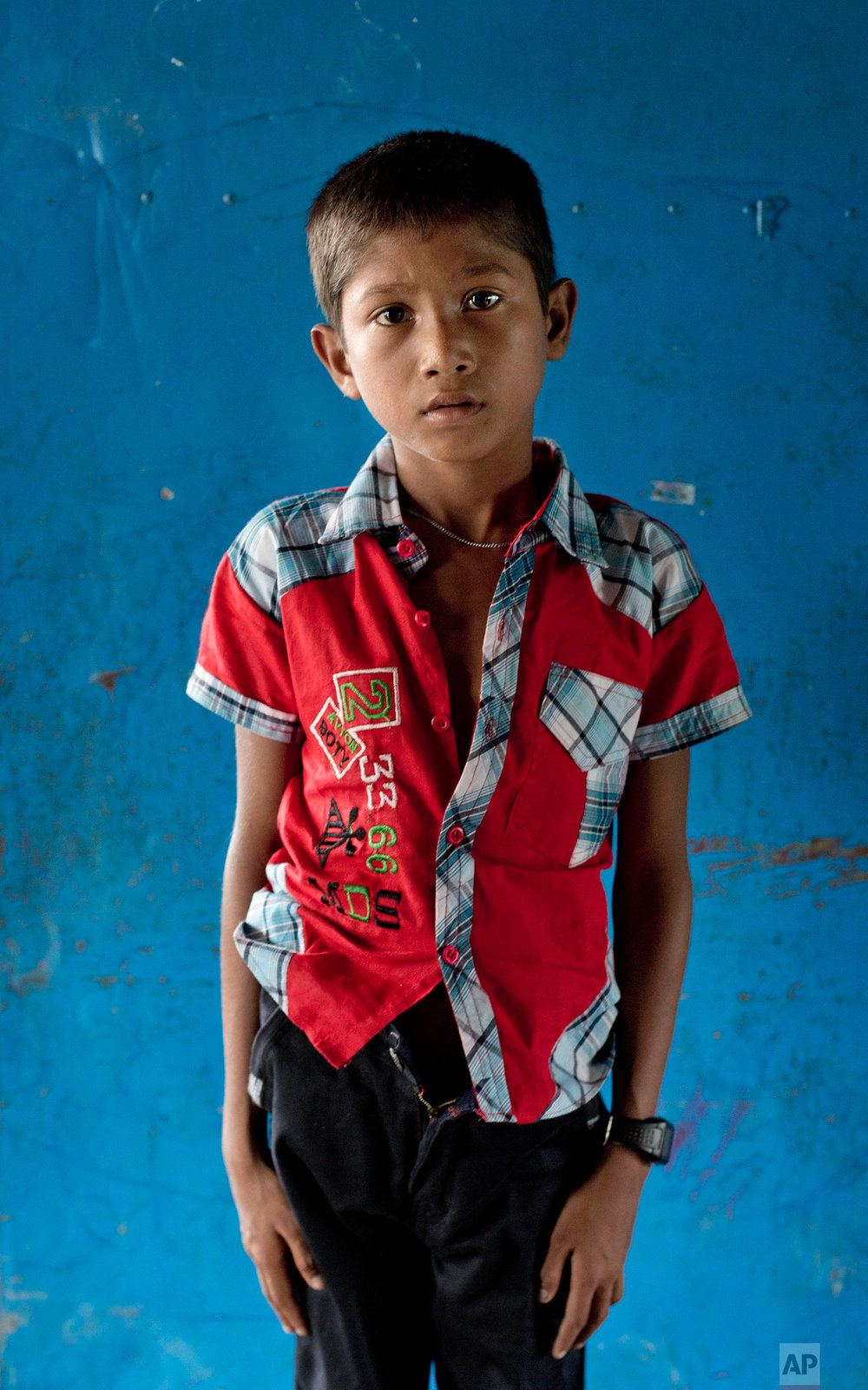 In this Oct. 1, 2017, photo, survivor of a boat capsize Mohamed Junaid, from Myanmar's Moidaung Village, stands for a photograph at a transit shelter at Kutupalong camp for newly arrived Rohingya refugees in Bangladesh. Junaid lost his mother and two siblings when the boat they were traveling on, to escape from Myanmar, capsized on Sept. 28. He survived along with his father Lalu Mia and two other siblings. (AP Photo/Gemunu Amarasinghe)