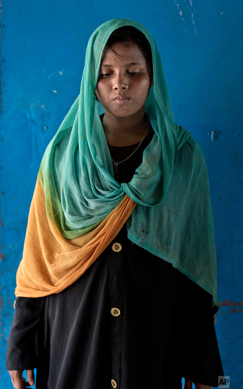 In this Oct. 1, 2017, photo, 18-year old survivor of a boat capsize Sazida Begum, from Myanmar's Moidaung Village, stands for a photograph at a transit shelter at Kutupalong camp for newly arrived Rohingya refugees in Bangladesh. Begum's mother and two sisters  drowned when a boat they were traveling in, to make their escape from Myanmar, capsized on Sept. 28. She survived along with her father Mohamed Kasim and three siblings. (AP Photo/Gemunu Amarasinghe)