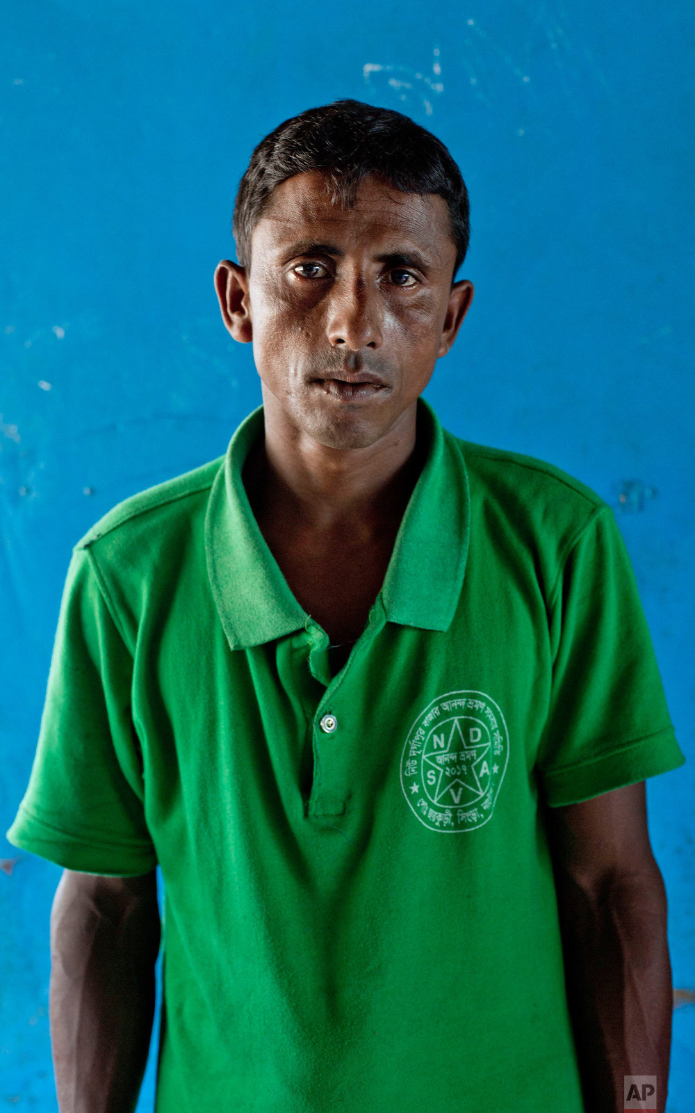 """In this Oct. 1, 2017, photo, a Rohingya Muslim man Sona Mia, from Myanmar's Moidaung village, stands for a photograph at Kutupalong camp for newly arrived Rohingya refugees in Bangladesh. Three of Mia's children aged six-months to six-years drowned when the fishing boat they traveling in, to escape from Myanmar to Bangladesh, capsized on Sept. 28. """"we will never go back,"""" Mia said on Myanmar. (AP Photo/Gemunu Amarasinghe)"""
