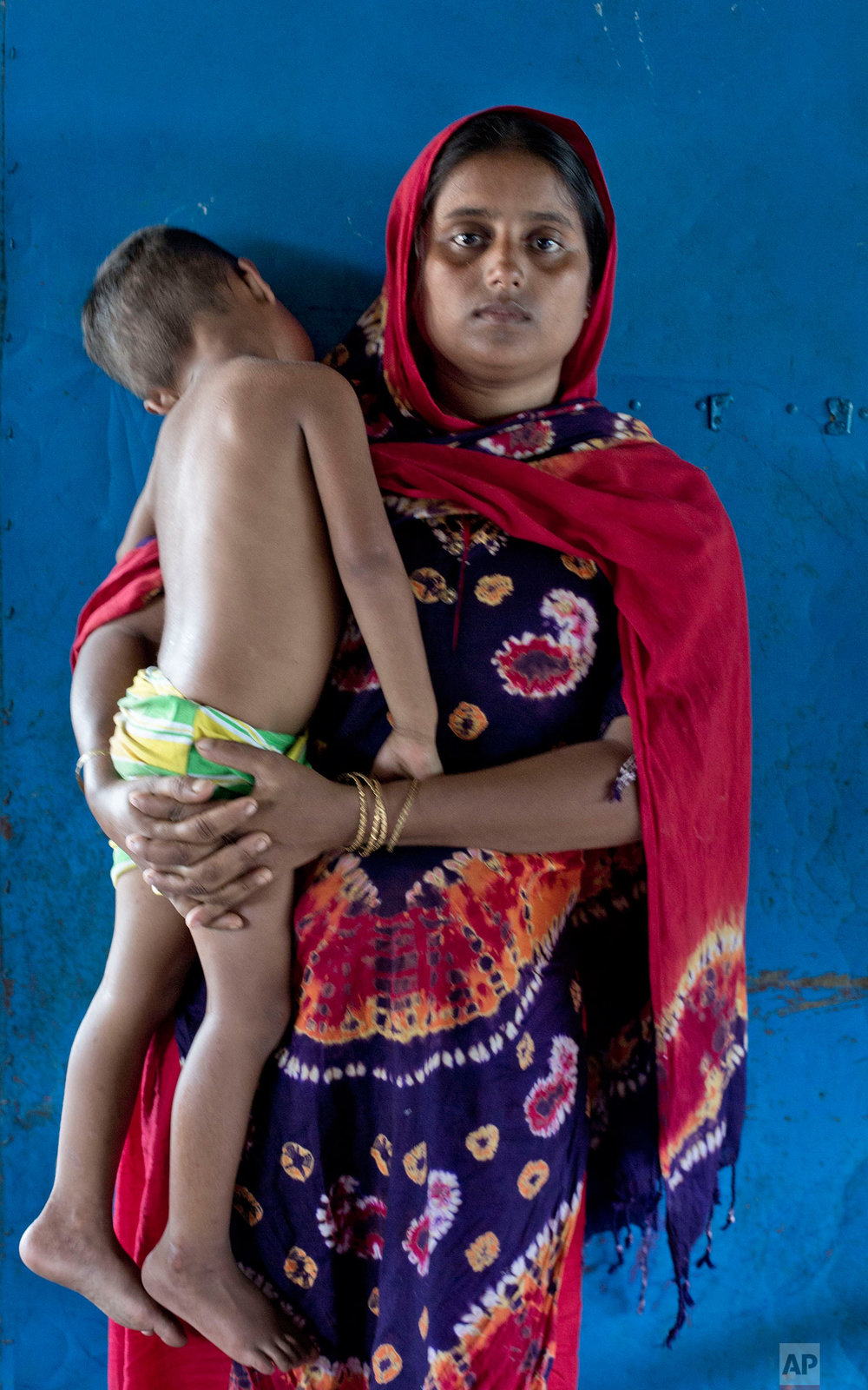 "In this Oct. 1, 2017, photo, 20-year-old Noor Fatima, from Myanmar's Moidaung Village, poses for a photograph with her son Abdul Rahaman inside a classroom serving as a transit shelter for newly arrived Rohingya refugees at Kutupalong camp in Bangladesh. Fatima, her husband 30-year old Abdul Salam, nine-month-old son Shaju Rahaman and Abdul Rahaman were passengers of the boat that capsized on Sept. 28. Shaju Rahaman was in Fatima's lap when the boat capsized. He died few hours after they were rescued. Asked if it was worth it, Fatima said ""I lost my child, but why would I want to go back to Myanmar? I want to forget about that country."" (AP Photo/Gemunu Amarasinghe)"