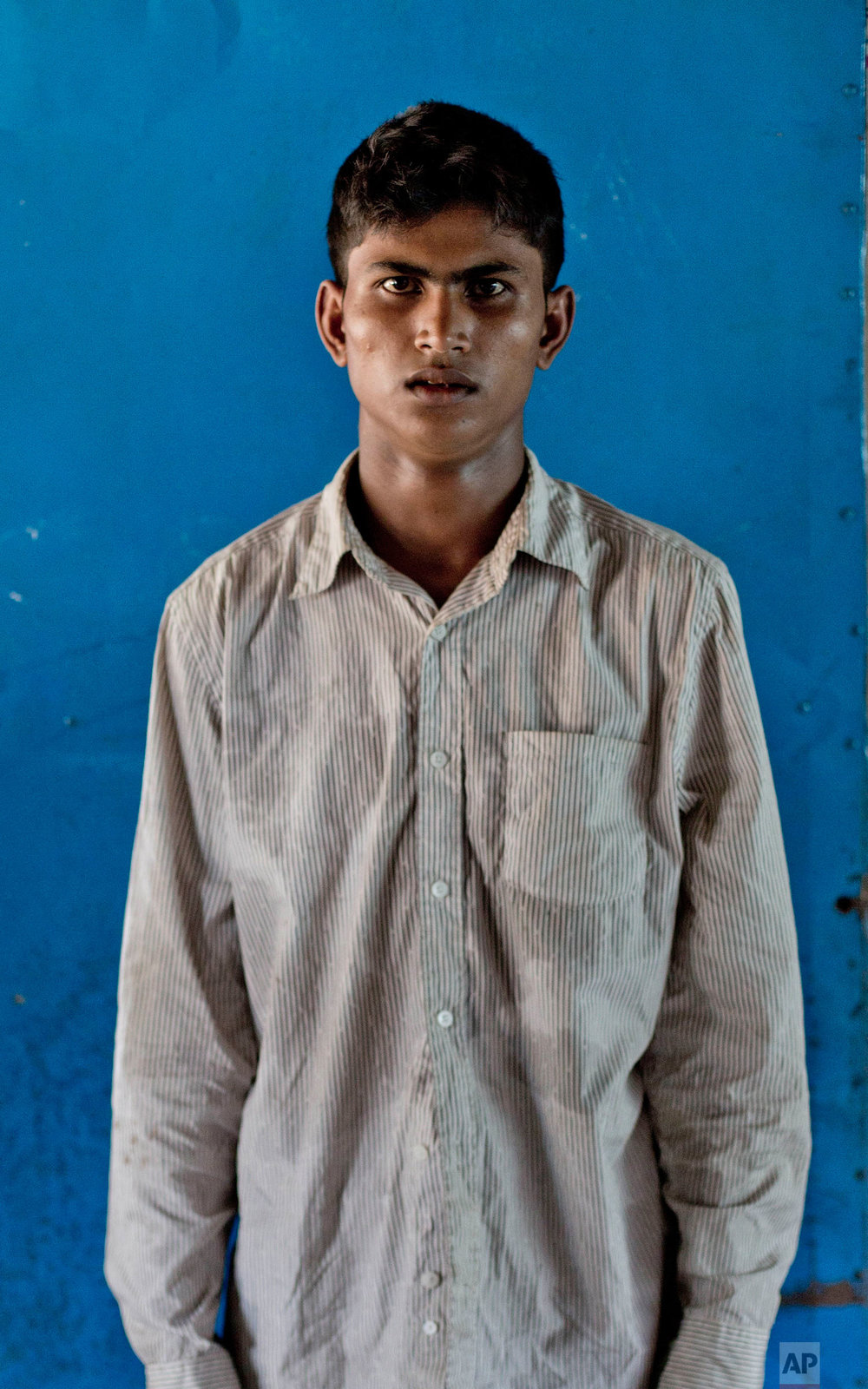 In this Oct. 1, 2017, photo, a 22-year-old Rohingya Muslim Nuro Salam, from Myanmar's Moidaung Village, stands for a photograph inside a classroom of a school serving as a transit shelter at Kutupalong camp for newly arrived Rohingya refugees in Bangladesh. Nuro's wife Sanzida and son drowned when the boat they were traveling in, to escape from Myanmar, capsized on Sept. 28. (AP Photo/Gemunu Amarasinghe)