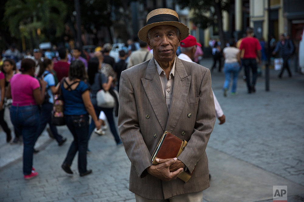 Retired English professor Roque Davis, 78, poses for a portrait in downtown Caracas, Venezuela, Monday, Oct. 23, 2017. (AP Photo/Rodrigo Abd)